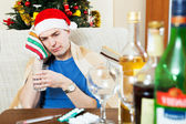 Young man with hangover in Santa hat — Stock Photo