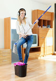 Cheerful woman in headphones  with mop — Foto Stock