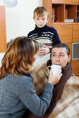 Unwell man surrounded by caring wife and son   — Stock Photo