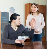 Husband counting money, woman watching — Stock Photo