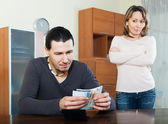 Man counting money, wife watching — Stock Photo