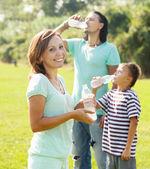 Koppel met tiener drinking water uit flessen — Stockfoto