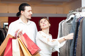 Couple with shopping bags choosing sweater   — Stock Photo