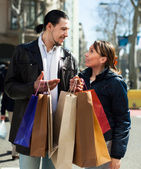 Man and girl with shopping bags at street — Stock Photo