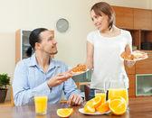 Happy couple having breakfast with croissants — Stock Photo