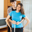 Guy measuring waist of girl — Stock Photo #48987195