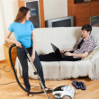 Woman cleaning while man resting — Stock Photo #48987223