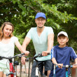 Happy family cycling through city — Stock Photo