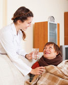 Nurse giving glass to woman — Stock Photo