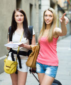 Girls with luggage and map — Stock Photo