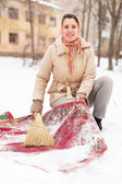 Woman cleans rug with snow — Stock Photo