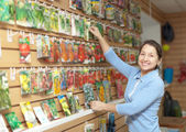 Woman chooses packed seeds at store — Stock Photo