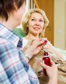 Retirement home employee offering mixture — Стоковое фото
