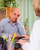 Elderly man with doctor in clinic — Stock Photo
