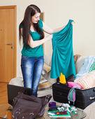 Brunette girl choosing dress for vacation   — Stock Photo