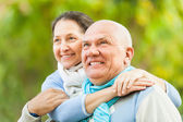 Mature couple against blured trees — Stock Photo