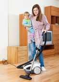 Mother with baby cleaning  home — Stock Photo