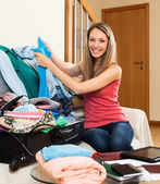 Woman putting clothes and accessories — Stock Photo