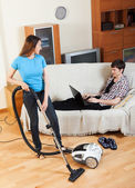 Woman cleaning while man resting — Stock Photo