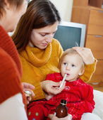 Two women caring for unwell baby   — Stock Photo