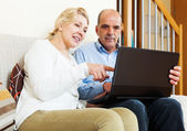 Happy mature couple with laptop — Stock Photo