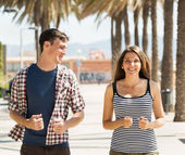 Smiling young couple running outdoor — 图库照片