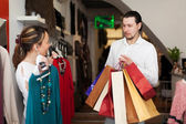 Smiling couple choosing clothes at boutique — Foto Stock