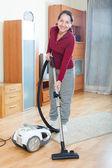 Happy mature woman vacuuming — ストック写真