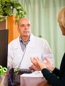 Mature doctor listening to female patient — Stock Photo