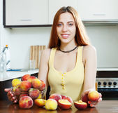 Beautiful woman with peaches at table — Stock Photo