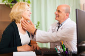 Mature doctor checking thyroid of woman — Stockfoto
