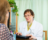 Mature  doctor assist female patient  — Stock Photo