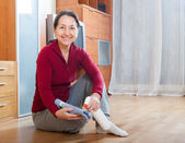 Mature  woman rubbing wooden floor — Foto de Stock