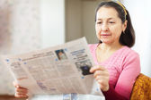 Serious  woman reading newspaper — Stock Photo