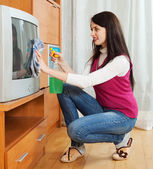 Brunette woman cleaning TV — Stock Photo