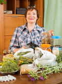 Mature woman with medicinal herbs — Stock Photo
