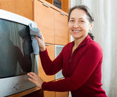 Mature woman cleaning TV   — Photo