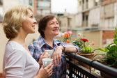 Old women on balcony with coffee — Stock Photo