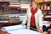 Woman works at  fabric store — Stock Photo