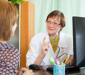 Mature doctor behind computer with patient — Stock Photo
