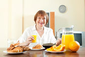 Mature  woman having breakfast — Foto Stock
