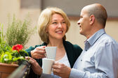 Aged couple drink tea on balcony — Stock Photo