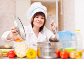 Woman in toque cooks with ladle — Stock Photo