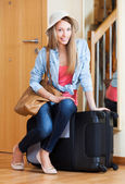 Woman with luggage near door — Stock Photo
