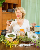 Mature woman with herbs at table — Stock Photo