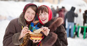 Girls  tasting pancake  during  Shrovetide — Stock Photo
