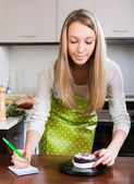 Girl in apron weighing cakes   — Stock Photo