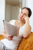 Wistful mature woman with newspaper — Stock Photo