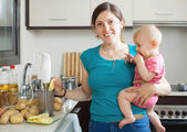 Woman with baby girl cooking — 图库照片