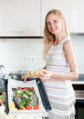 Pregnant housewife cooking trout — Stockfoto